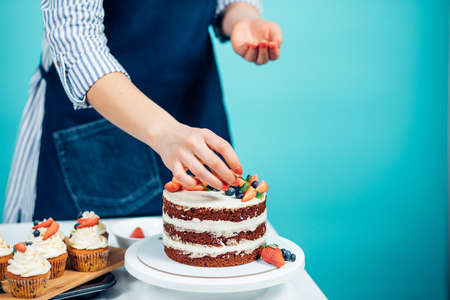 Cropped view of confectioner female hands putting strawberries on cake