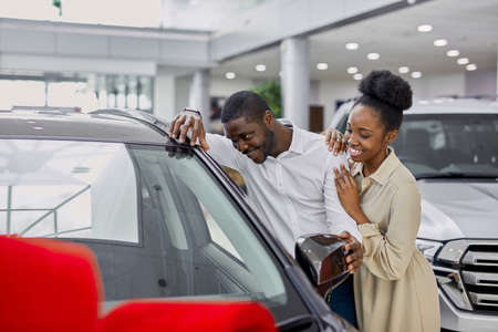 handsome dark-skinned man pleases his wife in dealership, he give car as a present, happy woman and man in love