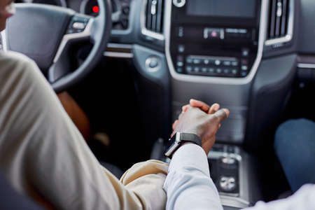 lovely black couple holds each others hand while sitting inside of car. in dealership Banco de Imagens