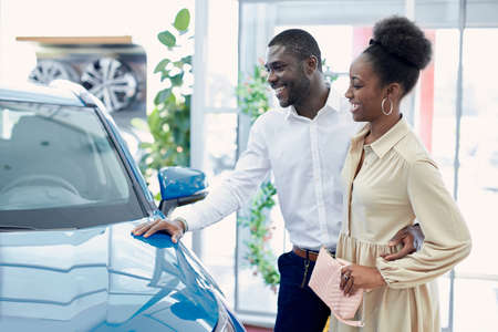 young african married couple in the search of the best car in dealership, they have conversation, discuss automobiles