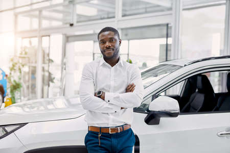 young black man happy with purchase in dealership, he is owner of represntative modern car, male looks at camera and smile