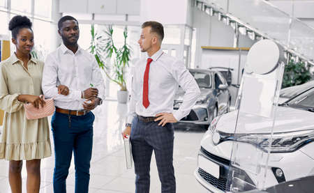 handsome young car salesman telling about the features of the car to african couple, beautiful married couple choose an auto