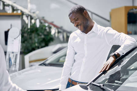 young african businessman ask questions about car presented in dealership, salesman explains and answer the questions, they sit on the hood and have friendly conversation
