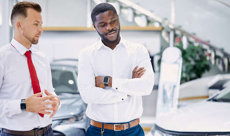 confident professional salesman talk about characteristics of car to customer man, black business man want to get necessary information about auto before making purchase, he asks questions