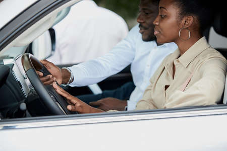 just imagine us on the road. portrait of happy african american couple checking out a car in modern dealership, they choose new car together