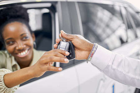 professional confident manager gives keys of new car to customer, client make purchase in dealership