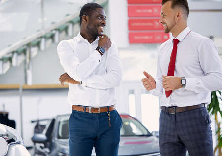 confident caucasian man salesperson selling cars at car dealership, he is presenting special offers to african american clients, have conversation