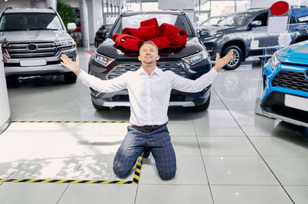 yeah, it is my car young caucasian man finally bought the car he dreamed about, he sits on the floor with hands up and shine with happiness