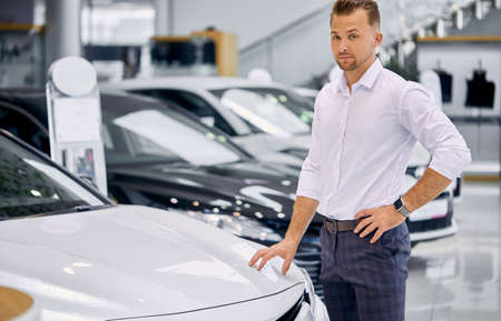portrait of happy caucasian client man buying new car in car store. luxurious white car is on exhibition in dealership