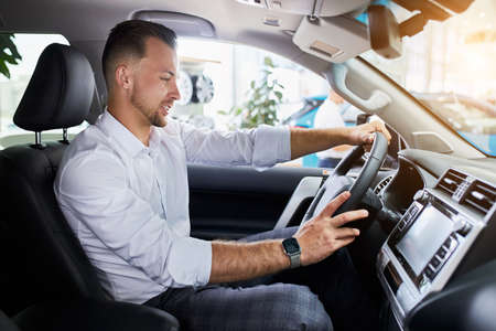 young caucasian handsome business man test drive new car. guy is examining new cars design and interior in car dealership