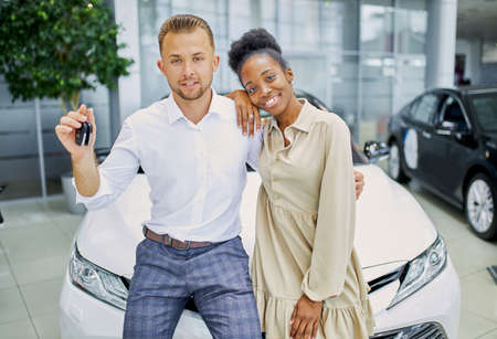 portrait of smiling married couple with keys from their new auto. diverse man and woman happy together, white luxurious car in the background