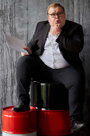 rich fat caucasian oilman looks at documents and thinks. man is in panic what to do with his oil company, where he needs to invest. current situation on global market is deplorable Reklamní fotografie