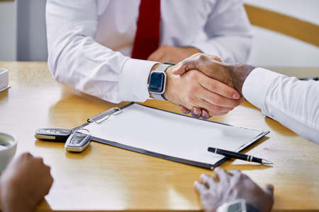 young caucasian dealer giving key to new african american owner and shaking hands in auto show or salon. auto business, car sale, deal, gesture and people concept