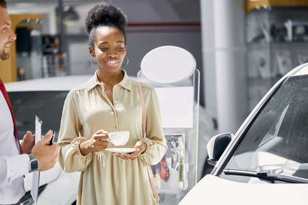 young attractive afro woman enjoy being owner of new auto, business lady make purchase in dealership 写真素材