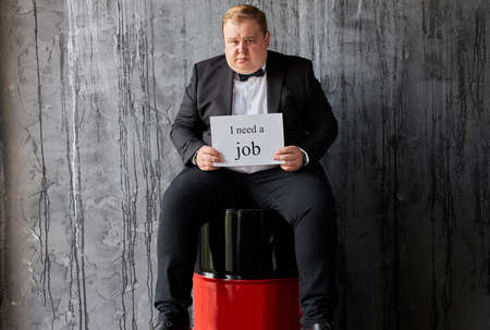 depressed fat caucasian oilman needs new job, his oil company is failed on world market, sits with barrels 写真素材
