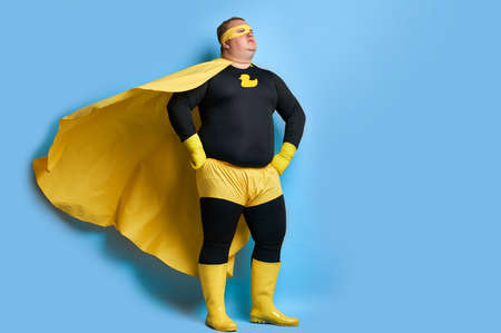 handsome brave strong man has a mad desire, a dream to shield the world from dirt and evil. fat superhero in yellow costume posing isolated over blue background