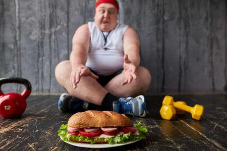 portrait of corpulent caucasian guy going to eat sandwich despite his overweight. junk food concept 写真素材