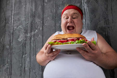 handsome caucasian fat man going to eat big tasty sandwich, he is not embarrassed by his excess weight, he eata what he wants
