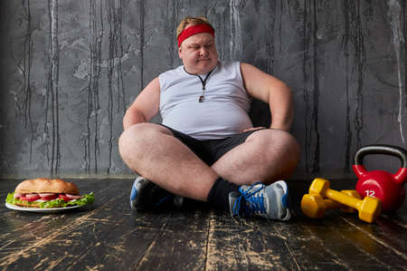 sad fat caucasian man is in a difficult position, man wants to eat a sandwich but his weight makes him exercise 写真素材