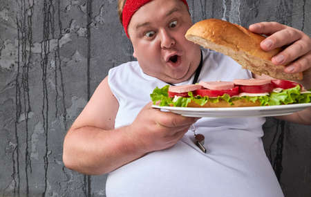 Wow fat man is surprised at a big sandwich, opens it and looks inside. handsome funny guy wants to eat after sport training
