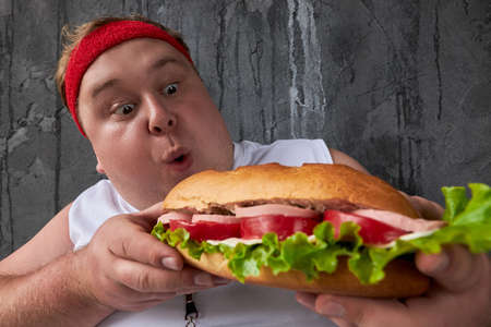 overweight caucasian man can not adhere to a healthy lifestyle and diet, doing sport exercises and at the same time eat unhealthy food