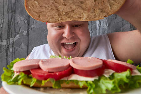 happy fat caucasian man is opening sandwich top, young man loves delicious food 写真素材