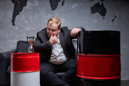 fat caucasian oil businessman thinks how to solve his oil business, he has no time. oil barrels next to him. oil industry, crisis concept Standard-Bild