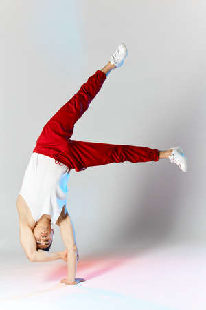 Chinese break dancer in red sweatpants showing his skills on white background, performing a handstand on stretched hands on white background