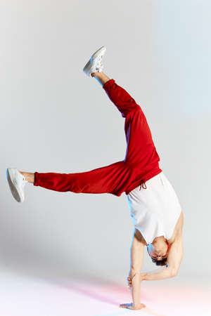 Chinese break dancer in red sweatpants showing his skills on white background, performing a handstand freeze, leaning on one stretched hand on white background