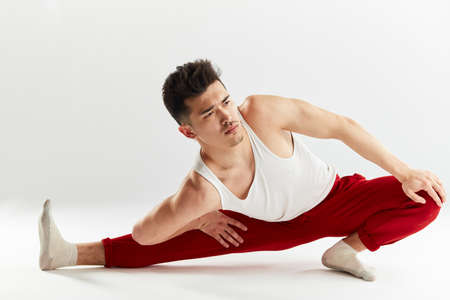 Asian man gymnastic in red sports sweatpants warming up isolated studio on white background Stok Fotoğraf