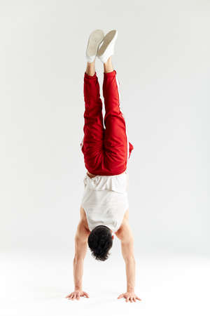 hip hop dancer doing handstand upside down with streched out arms and legs over white studio background