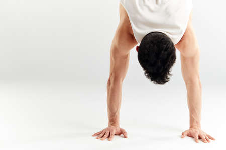 Cropped shot of dark-haired hip hop dancer doing handstand upside down with streched out arms over white studio background