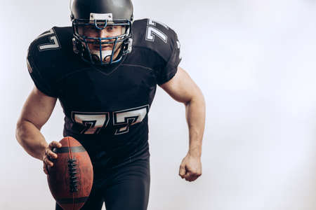 American football player wearing black helmet and jersey serving the ball in motion isolated over white background Фото со стока