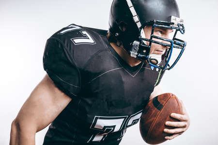 Isolated motion shot of American Football Quarterback player in professional protective black uniform and helmet passing a ball over white background.