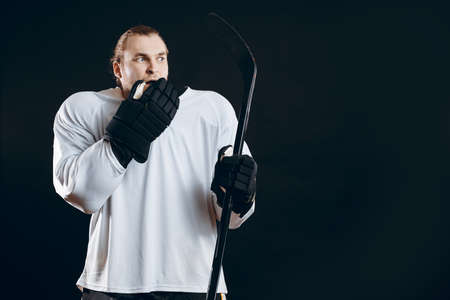Frightened hockey goalkeeper holding gaming stick touching his mouth with hand in protective glove shocked with missed goal. Sport, human emotions concept.