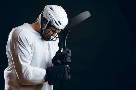 Isolated studio shot of serious concentrated hockey player with hockey stick prepares alone for important match, begging God to gove him luck and win. Professional sportsman with equipment