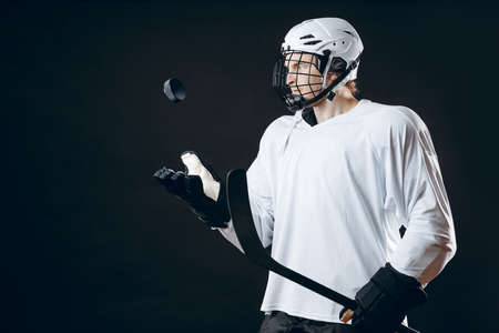 Hockey team trainer in white uniform and protective headgear on head throws a puck in the air, holding hockey stick over the black background with copyspace. Stock fotó