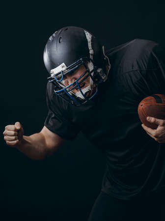 American football sportsman player in black outfit and helmet runing, isolated on black background