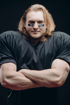 Portrait of confident fair-haired American football male player with war paint applied on his face looking at camera with crossed hand over black background