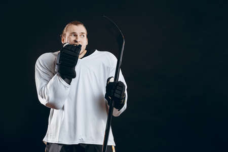 Frightened hockey goalkeeper holding gaming stick bites his hand in protective glove shocked with missed goal. Sport, human emotions concept.