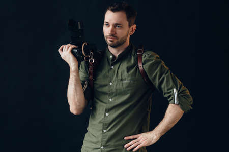 thoughtful serious man with hand on the hips is holding a camera, close up photo. creativity, creative ideas for photo session