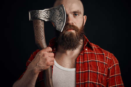 bearded man with mustache is holding a battle axe cover his eye and looking on camera on black background