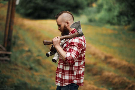 Bearded mohawk Man with firewoods and with axe on shoulder