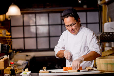 attractive cheerful Asian guy cutting a roll for clients. working hours in sushi bar . close up photo. copy space