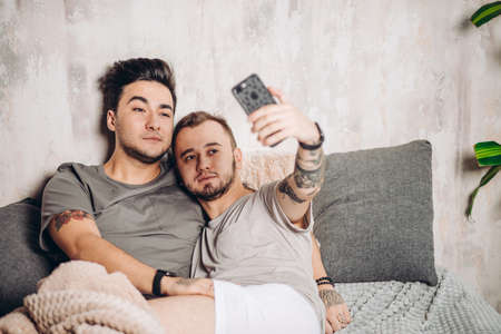 Happy handsome couple taking selfie in bed at home with modern loft interior