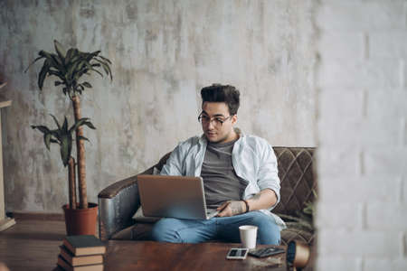 Bearded Hipster working Laptop modern Interior Design Loft Office.Man work Retro Sofa,Use contemporary Notebook,typing message.Blurred Background.Creative Business Startup Idea.Horizontal,Film