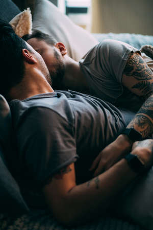 Caucasian homosexual family in bed before sleep. Handsome hot man with bristle kissing good night his sleepy male partner, lying in bed
