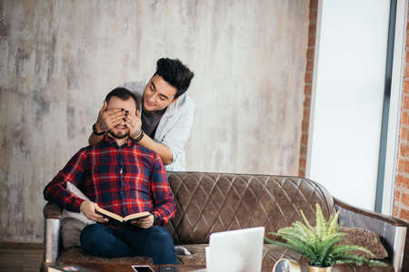 Happy same-sex couple sharing special moment of love. Lover man surprising his boyfriend with a present, embraces and closes his eye from behind. Romantic partners sit at loft monochrome interior. Archivio Fotografico