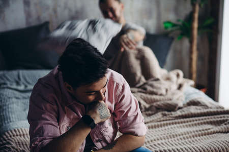 Young gay couple going through relationship problems. Pensive gloomy man dressed in t-shirt and underwear sits on bed with his hand leaning on chin with blurred image of his bridegroom on background