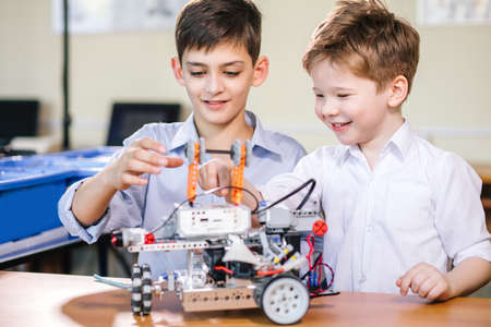 Two little curious technicians of various ages playing with robotic car toy at at a robot performance demonstration.